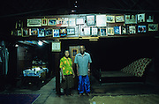 Batak couple with pictures of their relatives, stand inside their traditional home..Batak Indigenous Christian people living on Samosir Island and nearby Lake Toba in Indonesia. There are some 6 million Christian Batak in Indonesia, the world's largest Muslim country of 237 million people, which has more Muslims than any other in the world. Though it has a long history of religious tolerance, a small extremist fringe of Muslims have been more vocal and violent towards Christians in recent years. ..Batak religion is found among the Batak societies around Lake Toba in north Sumatra. It is ethnically diverse, syncretic, liable to change, and linked with village organisations and the monotheistic Indonesian culture. Toba Batak houses are boat-shaped with intricately carved gables and upsweeping roof ridges, and Karo Batak houses rise up in tiers. Both are built on piles and are derived from an ancient Dong-Son model. The gable ends of traditional houses, Rumah Bolon or Jabu, are richly decorated with the cosmic serpent Naga Padoha carved in wood or in mosaic, lizards, double spirals, female breasts, and the head of the singa, a monster with protruding eyes that is part human, part water buffalo, and part crocodile or lizard. The layout of the village symbolises the Batak cosmos. They cultivate irrigated rice and vegetables. Irrigated rice cultivation can support a large population, and the Toba and the Karo live in densely clustered villages, which are limited to around ten homes to save farming land. The kinship system is based on marriage alliances linking lineages of patrilineal clans called marga. In the 1820's Islam came to the southern Angkola and Mandailing homelands, and in the 1850's and 1860's Christianity arrived in the Angkola and Toba region with Dutch missionaries and the German Rheinische Mission Gesellschaft. The first German missionary caused the Dutch to stop Batak communal sacrificial rituals and music, which was a major blow to the traditional religi