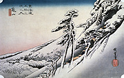 Kameyama:  from the series 'The Fifty-three Stations of the Tokaido', c1832. Coloured woodblock print.  Snow covered landscape with pine trees by steep pathwalking up to building at top.  Ando Hiroshige  also called Ando Tokutaro (1797-1858) Japanese artist and printmaker.
