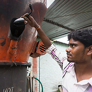 CAPTION: Checking on the combustion process inside one of DESI Power's gasifiers. LOCATION: Gayari, Araria District, Bihar, India. INDIVIDUAL(S) PHOTOGRAPHED: Ashish Kumar Yadav.