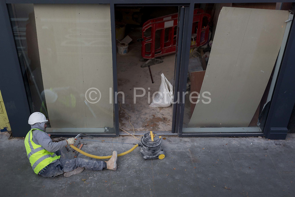 A construction worker uses a small industrial hoover to remove dust from a doorway of a new development in south London, on 10th October 2019, in Camberwell, Southwark, London, England.
