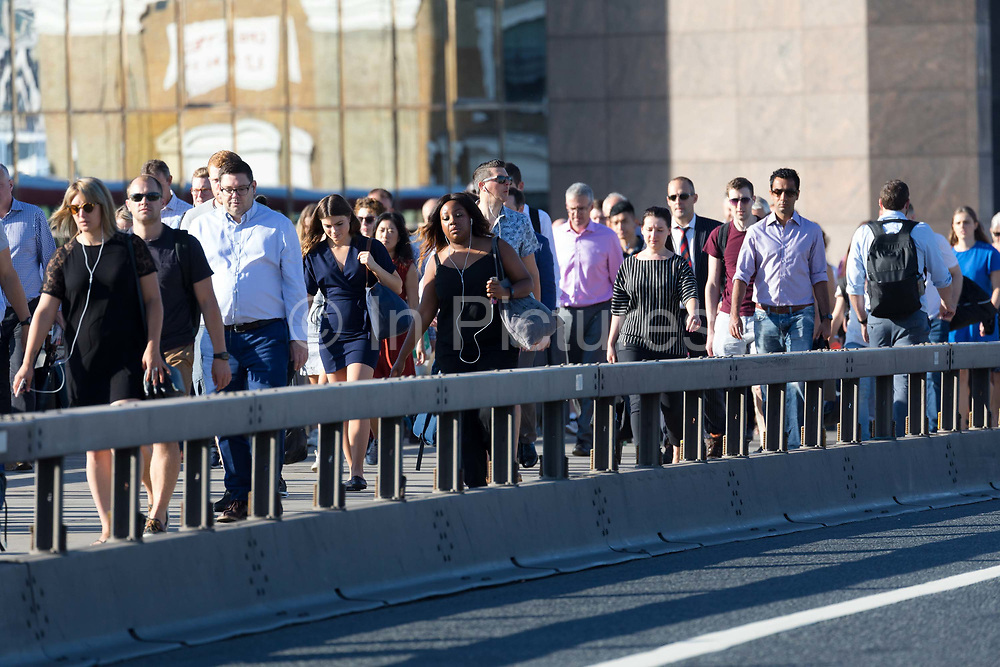 Commuters walk to work across London Bridge in London, England on August 03, 2018 during hot sunny weather as the heatwave continues in the capital and across Europe.