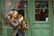 Clown figure playing a Saxaphone outside a restaurant. Honfleur, Normandy, France. . Honfleur is especially known for its old port, characterised by its houses with slate-covered frontages, painted many times by artists, including in particular Gustave Courbet, Eugène Boudin, Claude Monet and Johan Jongkind, forming the école de Honfleur (Honfleur school) which contributed to the appearance of the Impressionist movement. .<br /> <br /> Visit our FRANCE HISTORIC PLACES PHOTO COLLECTIONS for more photos to download or buy as wall art prints https://funkystock.photoshelter.com/gallery-collection/Pictures-Images-of-France-Photos-of-French-Historic-Landmark-Sites/C0000pDRcOaIqj8E