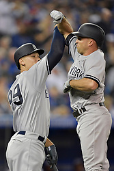 March 29, 2018 - Toronto, ON, U.S. - TORONTO, ON - MARCH 29: New York Yankees Right field Aaron Judge (99) jumps to congratulate New York Yankees Left field Brett Gardner (11) on his home run during the MLB season-opener game between the New York Yankees and the Toronto Blue Jays at Rogers Centre in Toronto, ON., Canada March 29, 2018. (Photo by Jeff Chevrier/Icon Sportswire) (Credit Image: © Jeff Chevrier/Icon SMI via ZUMA Press)