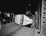 """Y-520410A-1. """"Wreck on Hawthorne Bridge. Drunk Indian & Radio Cab. April 10, 1952"""" (photographer's notes) Caption printed in Oregonian April 12, 1954 pg. 4: """"If Ed Jones, at right, had not left his cab ... the cab would not have been stolen and wrecked early Friday, as shown, on Hawthorne bridge. Alfred Smith, not shown, was arrested on charges of drunkeness and auto theft."""""""