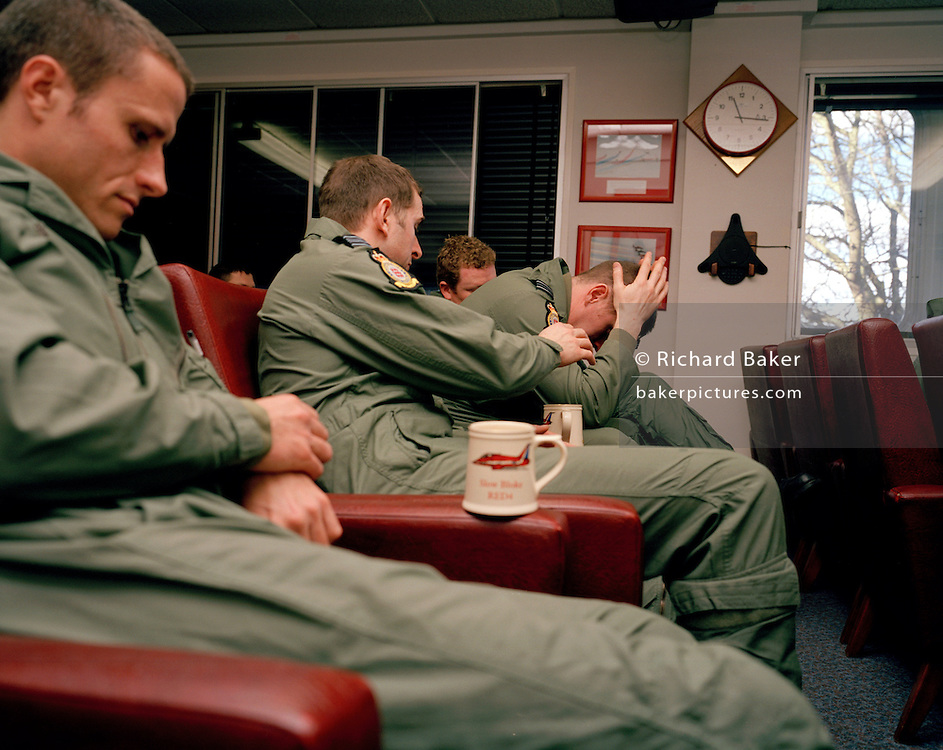 Pilots of the Red Arrows, Britain's RAF aerobatic team endure a post-flight de-brief in the squadron crew room at RAF Scampton.