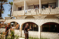 """Migrants and refugees stay at the Hotel Captain Elias in Kos, Greece on June 30, 2015. They must wait at the hotel for their documents to leave the island which can take anywhere around 15 days. The hotel is referred to as """"the camp"""" by the migrants, refugees and local authorities. Earlier this year, the greek island of Kos began receiving an influx of migrants and refugees fleeing their homes from countries such as Pakistan, Afghanistan and Syria. The local authorities of Kos established the abandoned Hotel Captain Elias, located on the outskirts of Kos Town, to act as a camp where the migrants and refugees would stay while they wait several days for their documents to leave the island. However, the camp lacked running water, electricity, enough beds, and sanitary cleanliness. Running water was restored only to the outdoor faucets and outdoor showers. Running electricity, enough beds and disease such as scabs caused by bed bugs still remain an issue at the camp. Nearly 100 migrants are housed in the camp; others who can afford to, stay in hotels for 10-15 euro a night because the conditions are better there."""