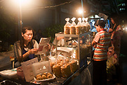 Night street scenes in Silom district of Bangkok. The bustling streets of this district are lined with street food stalls where dinner can be had for less than a dollar. These stalls are classic Bangkok. Busy, vibrant, the smells of cooking all around.