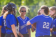 Middletown, New York - Middletown High School players meet before the start of an inning during a varsity girls' softball game on April 25, 2014.