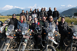 Lined up outside Pokhara with white peaks in the background; (front row L>R) Justin Big Meas Wilson, Danita Gayle, Christopher Galley, Jason Adamski, Tim Statt, Bear Haughton, Coolbeans Chris Marino, (back row L>R) Danger Dan, Pat Patterson, Geoff Kowalchuk, Buddi Singh, Mikey Revolt, Rob Galen, Gary Thomas, Patrick Lies, Chris Drew and Round the World Doug Wothke on Motorcycle Sherpa's Ride to the Heavens motorcycle adventure in the Himalayas of Nepal. On the third day of riding, we went from Pokhara to Kalopani. Wednesday, November 6, 2019. Photography ©2019 Michael Lichter.