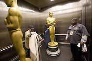 An Oscar statue inside a elevator is being moved into the press room for the Academy Awards show. Hollywood and Highland complex..Preparations for the 79th Academy Awards show begin outside the Kodak Theatre at the Hollywood and Highland Complex..A large Oscar statue was moved into place along with gold drapes outside the Kodak Theatre..