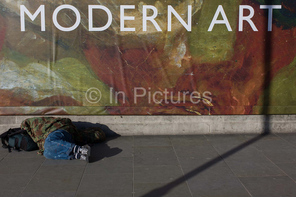 A sleeping man lies in front of the broad message on a hoarding announcing the next major exhibition by Delacroix at the National Gallery in London. As a scene of the classic and contemporary wealth, Art and Culture, we see the homeless man, seemingly asleep on the ground, beneath the large lettering announcing the major exhibition. Ferdinand Victor Eugène Delacroix (1798 – 1863) was a French Romantic artist regarded from the outset of his career as the leader of the French Romantic school.