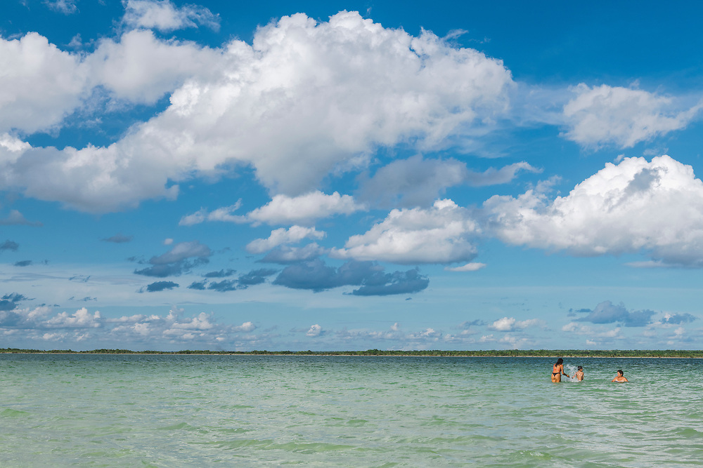 Bacalar, Mexico - June 2, 2021: Three people from Argentina -- a woman, her adult daughter, and her grandson --  enjoy a sunny afternoon at Bacalar Lagoon.