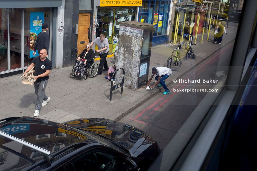 A youth bends down on the pavement in Camberwell on 10th July 2019, in south London England.
