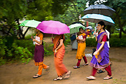 """Dance students walk from one lesson to another during the monsoon season at the highly prestigious Kalakshetra school for the arts, Chennai. The school was founded in 1936 and due to its exacting and demanding schedule is considered India's formost classical dance academy of this ancient cultural art heritage that is informally known as """"temple dancing"""" and that dates back to the Natya Shastra, the 2000 year old text that lays down the principles of Indian dramatic theory and performance. Tamil Nadu, India."""