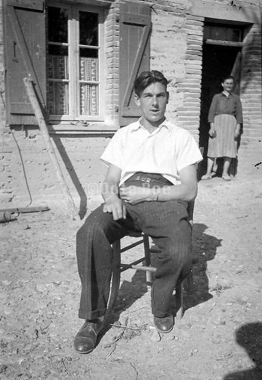 adult male sitting in front of house with mother in the background rural 1950s