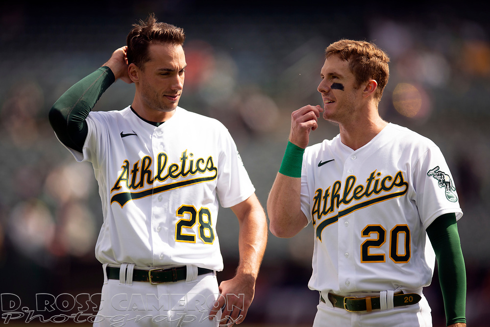 Sep 26, 2021; Oakland, California, USA; Oakland Athletics first baseman Matt Olson (28) and left fielder Mark Canha (20) commiserate at the end of the first inning against the Houston Astros at RingCentral Coliseum. Mandatory Credit: D. Ross Cameron-USA TODAY Sports