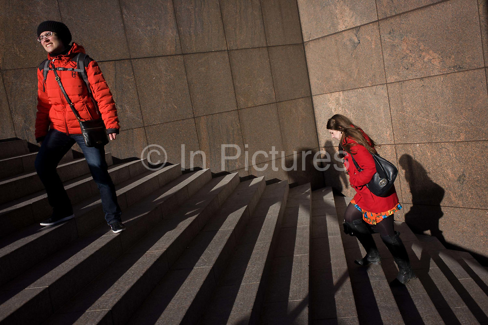 Two women both in red stand and climb city steps. Wearing matching red coats in winter sunshine, the two women are strangers to each other but have chosen the same hue of red. One stands squinting into the sun and the other concentrates on climbing the stairs with modern panelling and architecture in the background. The steps are located on the south side of London Bridge in the London borough of Southwark.