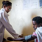 INDIVIDUAL(S) PHOTOGRAPHED: Sr. AskaleMariam Demisse (left) and Askalech Atnaf (right). LOCATION: Mecha Health Center, Bahir Dar, Ethiopia. CAPTION: Askalech Atnaf receives her first antenatal care service visit. The visit is performed by Sr. AskaleMariam Demisse, a Midwifery Nurse at the center.