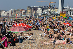Licensed to London News Pictures. 08/09/2021. Brighton, UK. Last chance of sun. Sunbathers enjoy 28c on busy Brighton Beach, East Sussex today. Weather forecaster predict an end to the hot weather as thunderstorms are set to hit England tonight. Photo credit: Alex Lentati/LNP