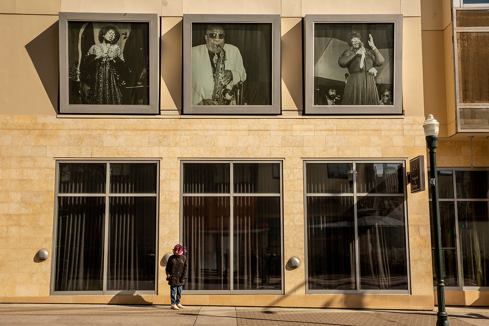 Charlotte Hubbard, a native of San Francisco and longtime neighborhood resident, waits for the bus in front of the Fillmore Heritage Center in the Western Addition neighborhood on Thursday, Feb. 7, 2019, in San Francisco, Calif. The heritage center used to feature a photo of Hubbard's father, native San Franciscan and jazz musician Junius Simmons.