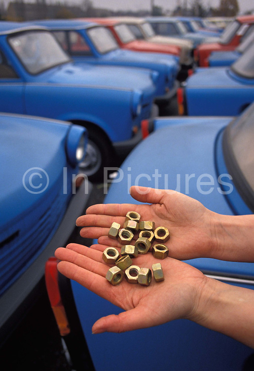 Six months after the fall of the Berlin Wall, a pair of hands cup some nuts that go towards the construction of Trabant cars at the car factory in the former East Germany DDR where the last Trabants await buyers outside the factory production line, on 1st June 1990, in Zwickau, eastern Germany former DDR. The DDR-produced Trabant suffered poor performance, but its smoky two-stroke engine regarded with affection as a symbol of the more positive sides of East Germany. Many East Germans streamed into West Berlin and West Germany in their Trabants after the opening of the Berlin Wall. It was in production without any significant change for nearly 30 years. The name Trabant means fellow traveler in German.