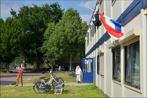 Nederland, Grave, 13-6-2015Open dag bij het AZC, azielzoekerscentrum. Een van de jongeren die hier verblijven heeft eindexamen gedaan.Vlag met boekentas is uitgehangen. Deze week hebben scholieren van het voortgezet onderwijs de uitslag van hun eindexamen gekregen. Bij veel geslaagden gaat traditioneel de vlag uit, met de schooltas aan het einde van de stok.Open dag in het azc generaal de Bons, voorheen een kazerne. Het coa organiseert dit samen met vluchtelingenwerk. Veel vrijwilligers helpen bij de opvang van vluchtelingen en azielzoekers. Veel culturen leven naast elkaar waronder mensen uit Syrie, syrië, Irak, eritrea, somalie.The Netherlands, Grave, 13-6-2015Open day at the AZC, refugee center. One of the young people who stay here have done graduation.Flag is hung. This week, students schools received the results of their exams. Traditionally the flag and schoolbag is hung ou.Open day at the reception center General de Bons, a former barracks. The coa organizing this with refugee work. Many volunteers help with the reception of refugees and asylum seekers. Many cultures live side by side ones, including people from Syria, Syria, Iraq, Eritrea, Somalia. Foto: Flip Franssen/Hollandse Hoogte