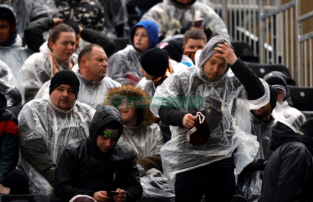 Fans shelter from the rain under a poncho in the Graham Hughes stand during the Premier League match at Molineux, Wolverhampton.
