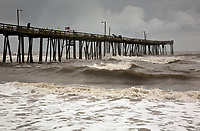NC01271-00...NORTH CAROLIINA - Fishing on the Nags Head Pier in the face of a large storm coming in over the Atlantic Ocean.