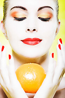 beautiful caucasian woman portrait holding a orange holding a orange smiling in studio on yellow background