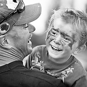 A young boy with a painted face smiles as his father holds him. Missoula Photographer