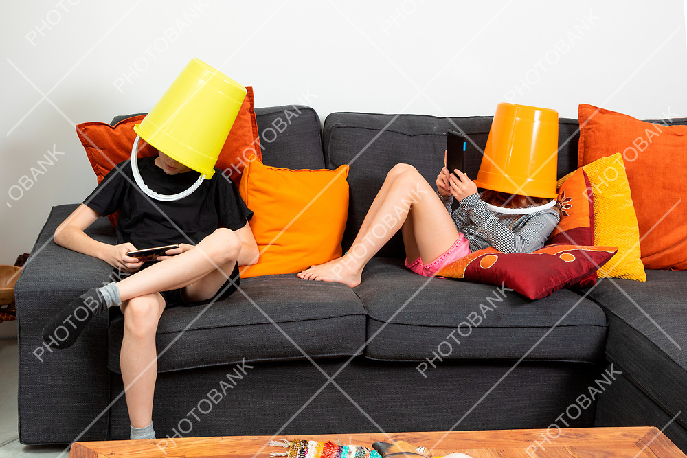 Brother and sister sitting on a sofa at home with a bucket on their heads playing with tablets. Concept of absence of communication