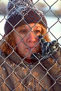 Homeless woman age 50 peering through chain link fence. St Paul Minnesota USA