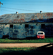 "VW van parked opposite redundant farm buildings near Clarksdale. If you want to explore Clarksdale and the Blues country in true retro fashion the best place to do so is by staying at the Shack Up Inn. In The Promised Land: The Great Black Migration and How It Changed America, author Nicholas Lemman describes how, on Oct. 2, 1944, a crowd of 3,000 people quietly watched the first public demonstration of the mechanical cotton picker at Hopson's plantation in Clarksdale. At best, wrote Lemman, a skilled field hand could pick 20 pounds of cotton in an hour; the mechanical picker picked 1,000 pounds. Hopson calculated that a bale of cotton (500 pounds) cost $39.41 to pick by hand and $5.26 by machine. It wasn't too hard to foresee the future. Hopson was the first plantation to convert completely to the mechanical cotton pickers. Soon afterward, the sharecropper shacks where the plantation's workers had lived were abandoned and then torn down. But now they're back at the Shack Up Inn, Mississippi's oldest B&B -- and that's bed and beer, y'all. ""We don't fool around with any fixing of breakfasts,"" said Bill Talbot, part owner of the inn."