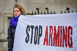 """© Licensed to London News Pictures. 07/02/2017. London, UK. Campaigners hold a banner reading """"STOP ARMING SAUDI""""  at the entrance to the Royal Courts of Justice in London, where a the group Campaign Against Arms Trade is challenging the legality of UK arms exports to Saudi Arabia.  Photo credit: Ben Cawthra/LNP"""