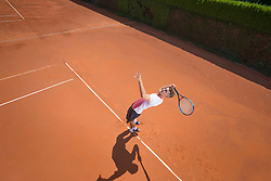 Young male tennis player serving the ball on sunny red tennis court, Bavaria, Germany