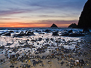 The sun sets over the Pacific Ocean near winter solstice at Three Arch Rocks, Oceanside, Oregon, USA. Sunset sky glows orange and magenta.
