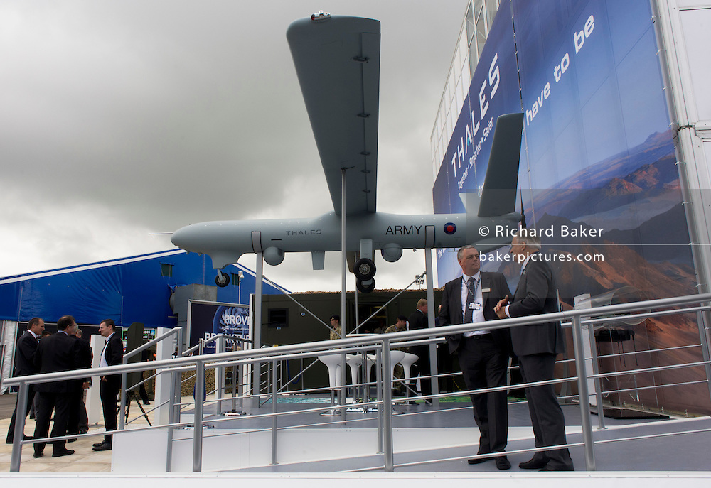 """Company employees at defence, security and aerospace company Thales' exhibition stand at the Farnborough Air Show. The MoD's newest and most sophisticated surveillance and targeting drone, the Watchkeeper, is undergoing trials at Aberporth in west Wales. While the arguments over America's policy of """"assassination by drone"""" rage across Pakistan and Afghanistan, fuelling public concern over the cold-eyed automation of warfare, the future of UAVs is quietly taking shape here on the Welsh coast, where there is daily proof that UAVs and manned aircraft can co-exist in British airspace."""
