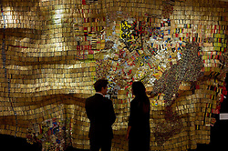 © Licensed to London News Pictures. 21/04/2011 London, UK. A Bonhams staff member with a hanging tapestry titled 'New World Map' by Ghana's El Anatsui. The 11ft  by 16ft work goes to auction next week as part of the Modern and Contemporary African Art sale and is expected to fetch between £500,000 to £800,000..Photo credit : Simon Jacobs/LNP