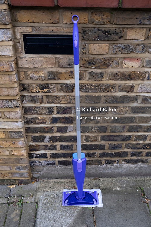A discarded Flash Speedmop stands upright against the wall of a suburban house in a residential south London Street, on 1st November 2020, in London, England.