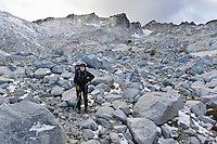 A woman backpacker standing in a boulder / talus field in the Upper Enchantment Lakes Wilderness area, Cascade mountains, Washington, USA.