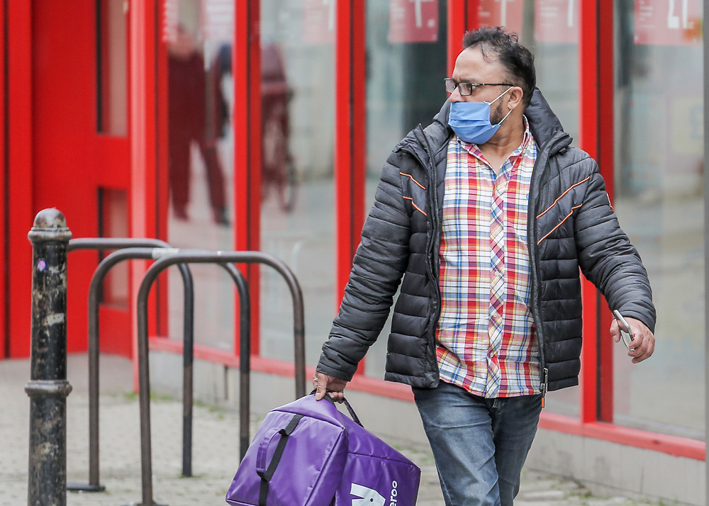 12th, March, 2021. Cheltenham, England. A Deliveroo rider walks through the town centre wearing a mask.
