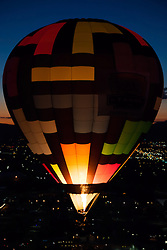 """""""Dawn Patrol 12"""" - Photograph of a glowing hot air balloon flying for the Dawn Patrol at the 2012 Great Reno Balloon Race. Photographed from a hot air balloon."""