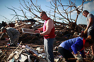Terry Wallace looks at a family name sign from his mother-in-law's tornado-destroyed home across the street from the Plaza Towers elementary school in Moore, Oklahoma May 22, 2013. A massive tornado tore through a suburb of Oklahoma City, wiping out whole blocks and killing at least 24.   REUTERS/Rick Wilking (UNITED STATES)