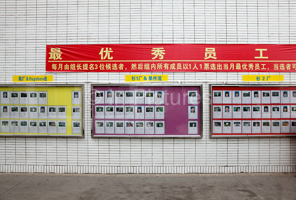 Pictures of model employees hang a wall at the Textile Alliance Apparel factory in Qingxi Township, Dongguan, Guangdong Province, China, on July 28, 2010. The factory supplies shirts and pants to major brands such as J Crew, Hugo Boss, Burberry, etc and produces over 300,000 shirts per day.