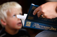 Joshua Jeub, 3, looks at his father Chris holding a bible during a worship gathering in the family home in Monument, Colorado Sunday July 19, 2009. Quiverfull believers Wendy and Chris Jeub have 15 children and would be happy to have more if God wills it they say. Picture July 19, 2009. REUTERS/Rick Wilking (UNITED STATES SOCIETY RELIGION)