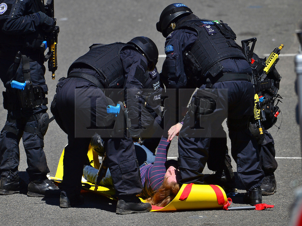© Licensed to London News Pictures. 30/06/2015. London, UK. Armed police on the scene helping an injured women. . Members of the emergency service take part in a mocked-up terrorist firearms attack at Aldwych station in central London. The exercise is the biggest to take place in London and is happening a week after dozens of people where killed when a gunman opened fire on a beach in Tunisia.  Photo credit: Ben Cawthra/LNP