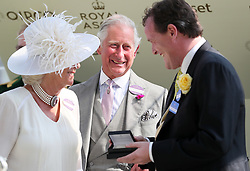 The Prince of Wales smiles as he presents trainer Richard Hannon Jr with his prize after wining the St James's Palace Stakes during day one of Royal Ascot at Ascot Racecourse.