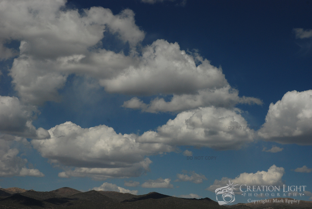 """Cumulus clouds are a type of cloud with noticeable vertical development and clearly defined edges. Cumulus means """"heap"""" or """"pile"""" in Latin. They are often described as """"puffy"""" or """"cotton-like"""" in appearance. Cumulus clouds may appear alone, in lines, or in clusters."""