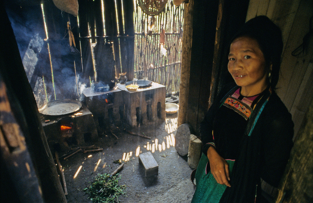 A woman from the Dong ethnic minority group waits to start meal preparations at the doorway to her kitchen as the evening light pours in through the wooden Dong architecture of her home in southern China's Guizhou province.