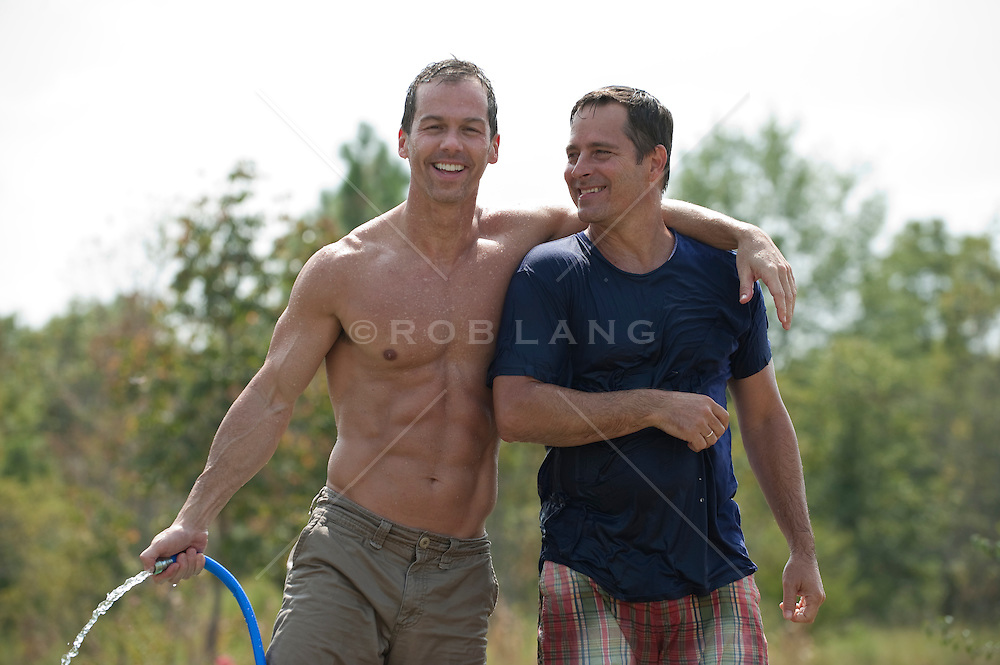 Two man after a water fight with a garden hose
